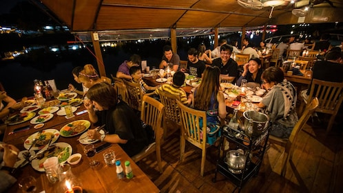 Guests enjoying their dinner aboard the Ping River Dinner Cruise in Chiang Mai