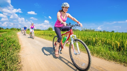 Female tourist riding bike down dirt path in grass field with others riding behind.