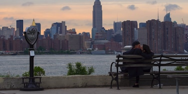Lovers watching sunset with Empire State Building on the background in the East River State Park in Williamsburg, Brooklyn. #LikeALocal