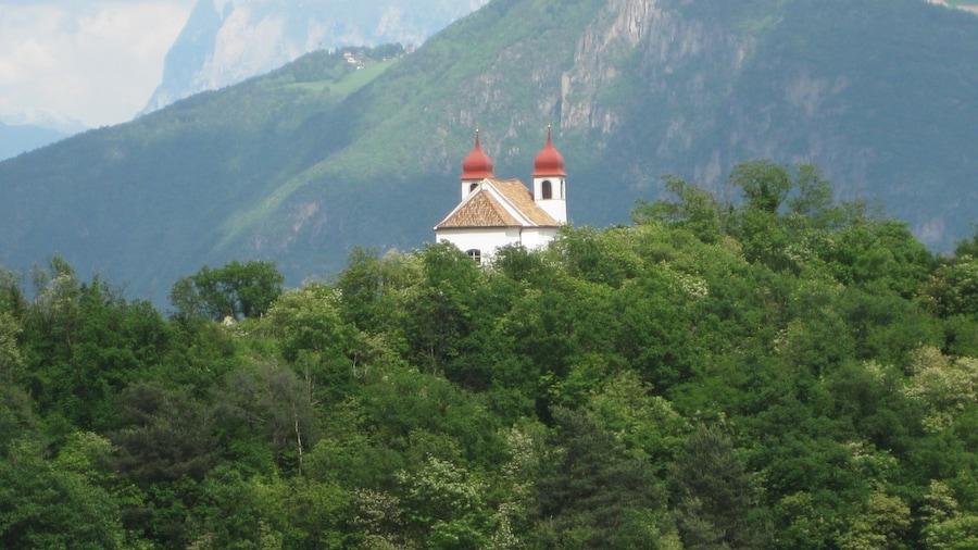 """Photo """"Die Heiligkreuzkirche auf der Gleif (auch einfach Gleifkirche genannt) in Eppan in Südtirol von Westen gesehen, im Hintergrund der Schlern"""" by undefined (Creative Commons Zero, Public Domain Dedication) / Cropped from original"""