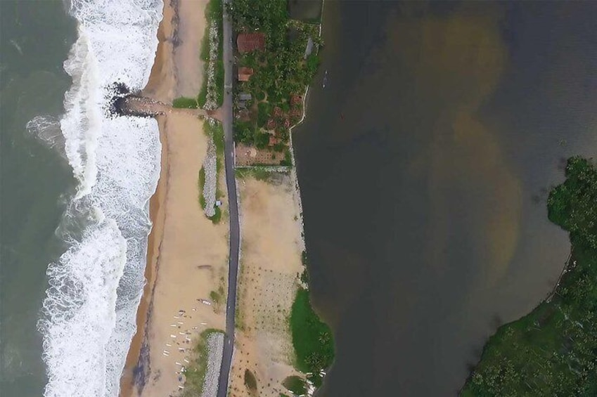 Arabian Sea and Paravur Lake separated by a long strip of sandbar where Syzygy is located.