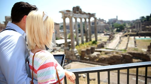 Young couple gazing onto the ancient Roman Forum.