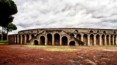 Landscape photo of the exterior of an amphitheater in Pompeii.