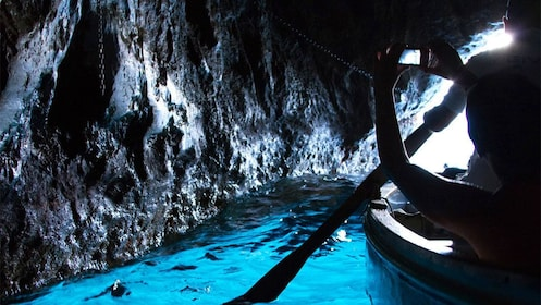 Tourists boating through The Blue Grotto sea cave on the coast of Capri in southern Italy