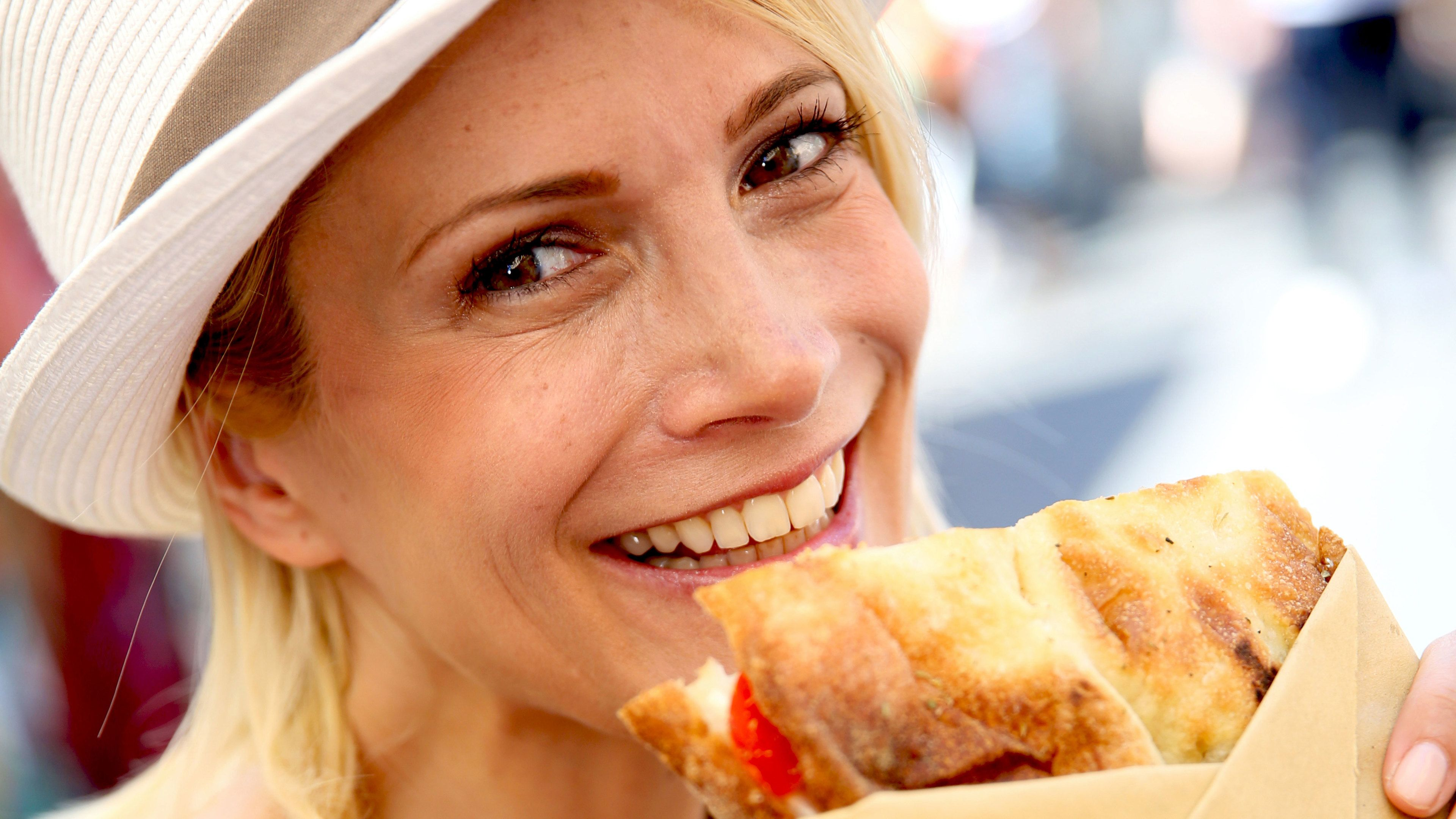 Woman enjoying a baguette from a shop in the Jewish Ghetto of Rome.