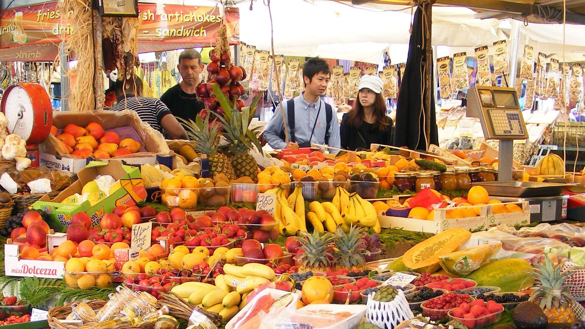Couple tourists strolling through the food market at Campo de Fiori.