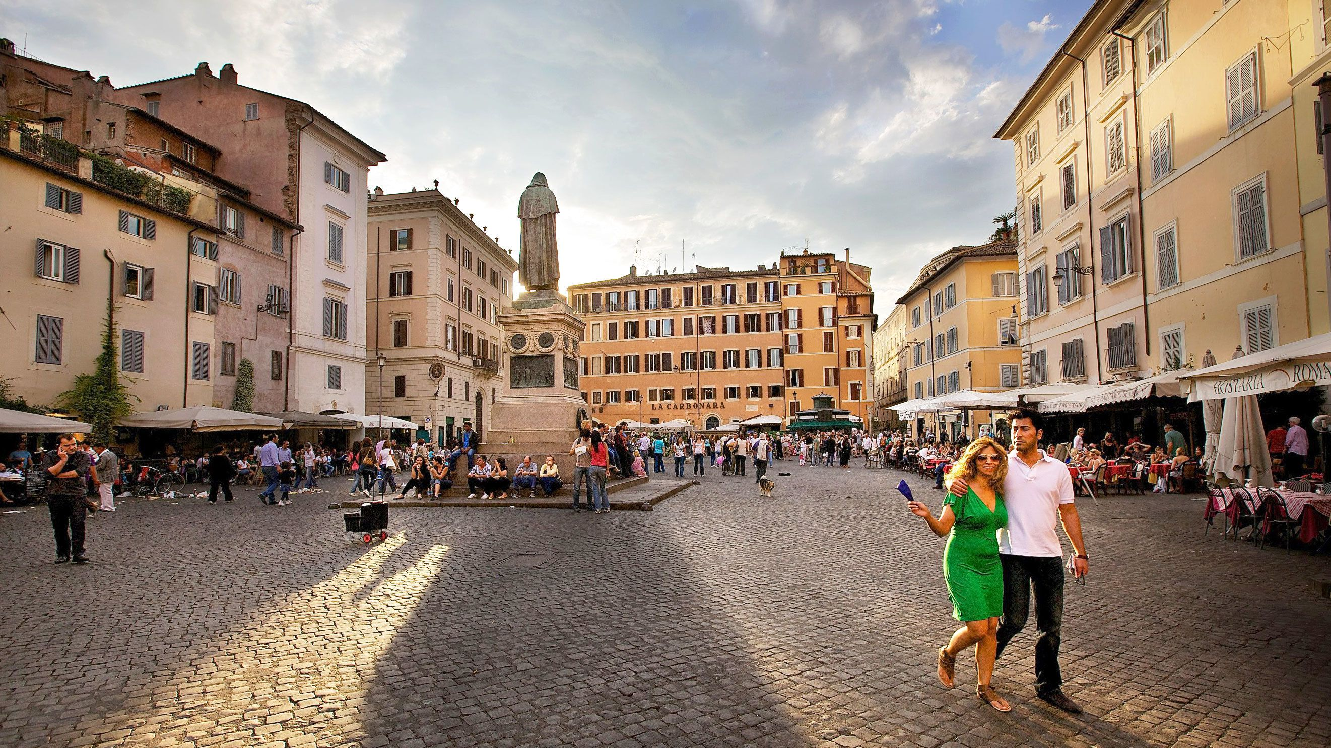 Photo of a couple strolling through the Trastevere in Rome as the sun sets.
