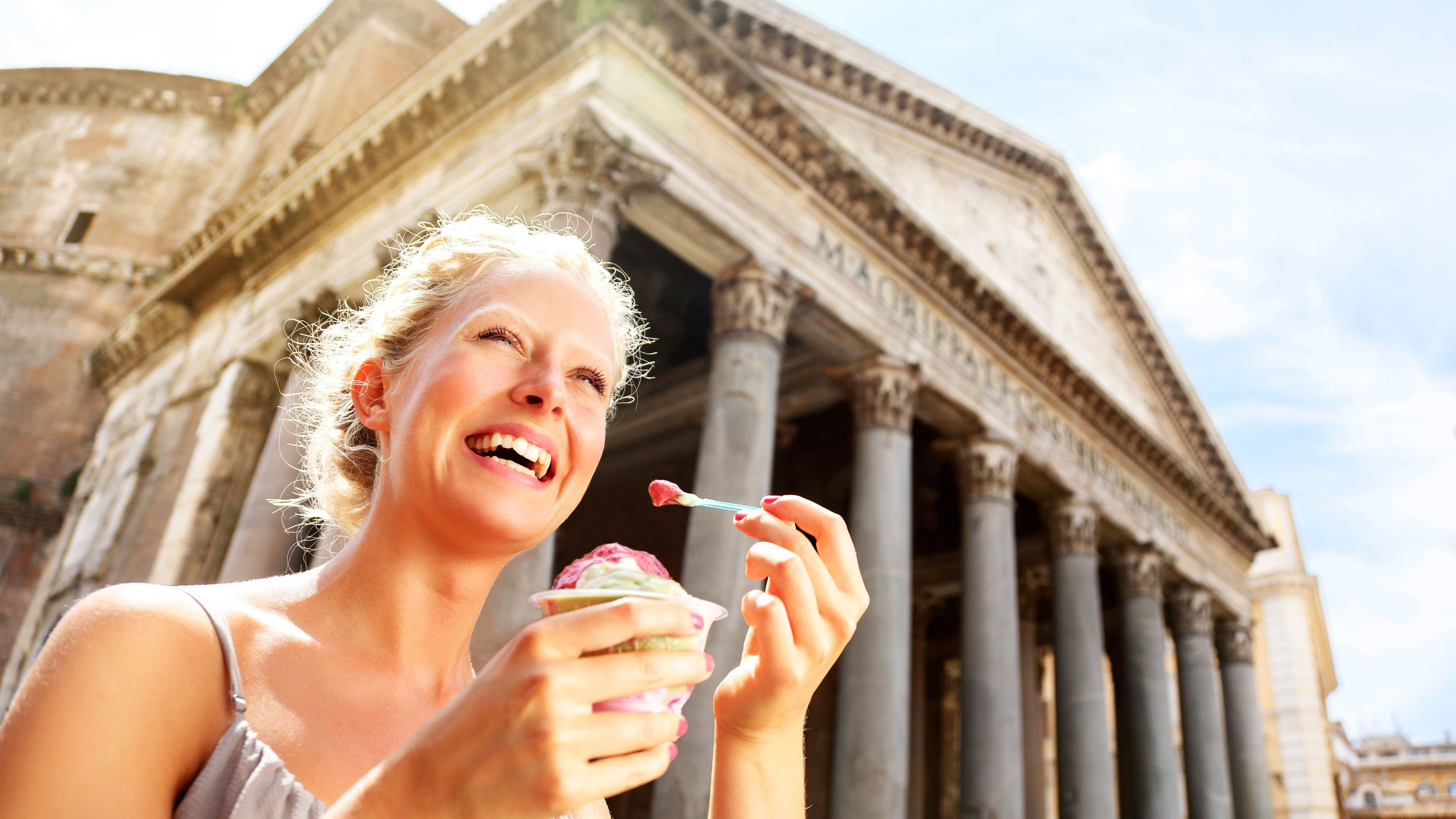 Woman enjoying a cup of gelato in front of the Pantheon in Rome, Italy.