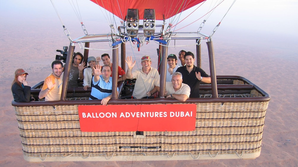 Show item 3 of 6. eleven people in a hot air balloon basket far above ground in Dubai