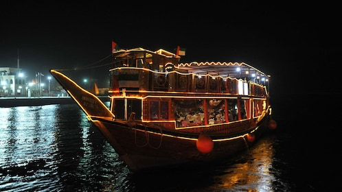 dinner boat lit up at night in Dubai