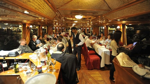 dinner boat filled with passengers seated at tables in Dubai
