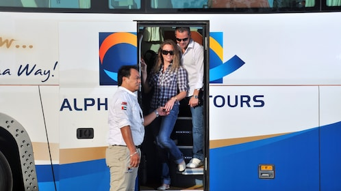 man and woman stepping off touring bus in Dubai
