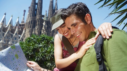 happy couple looking at city map of Barcelona
