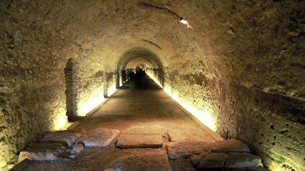 people walking down tunnel beneath Tarragona Cathedral church in Barcelona