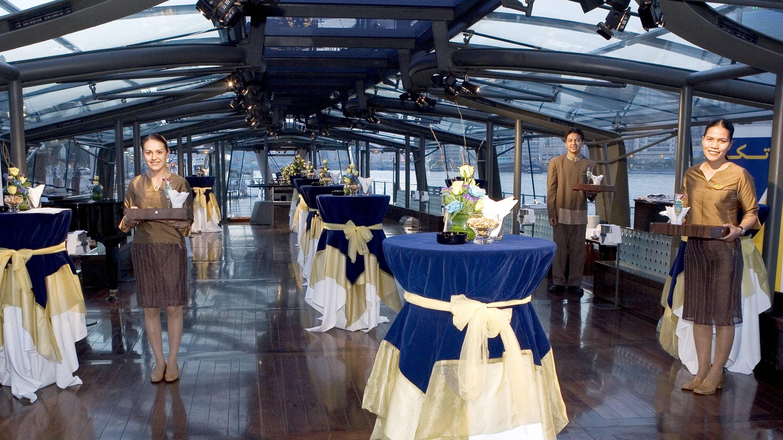 waitress awaiting passengers to board tour boat in Dubai