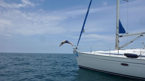 man diving off bow of sailboat on Mediterranean in Barcelona