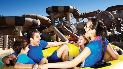 group of four going down water slide in an inner tube at water park in Dubai