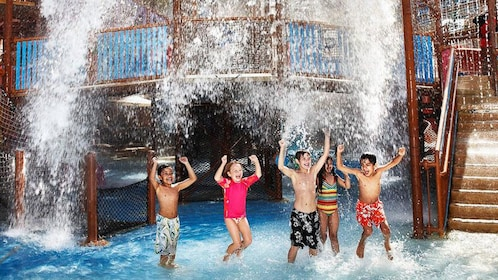 five kids laying underneath waterfall at waterpark in Dubai