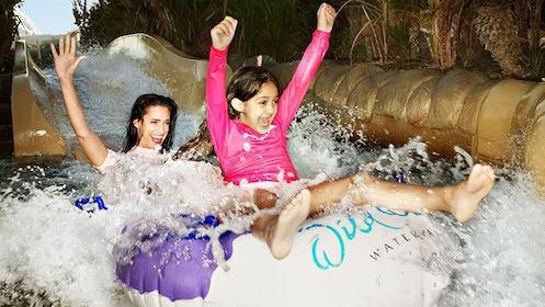 woman and young girl ride inner tube down slide at water park in Dubai