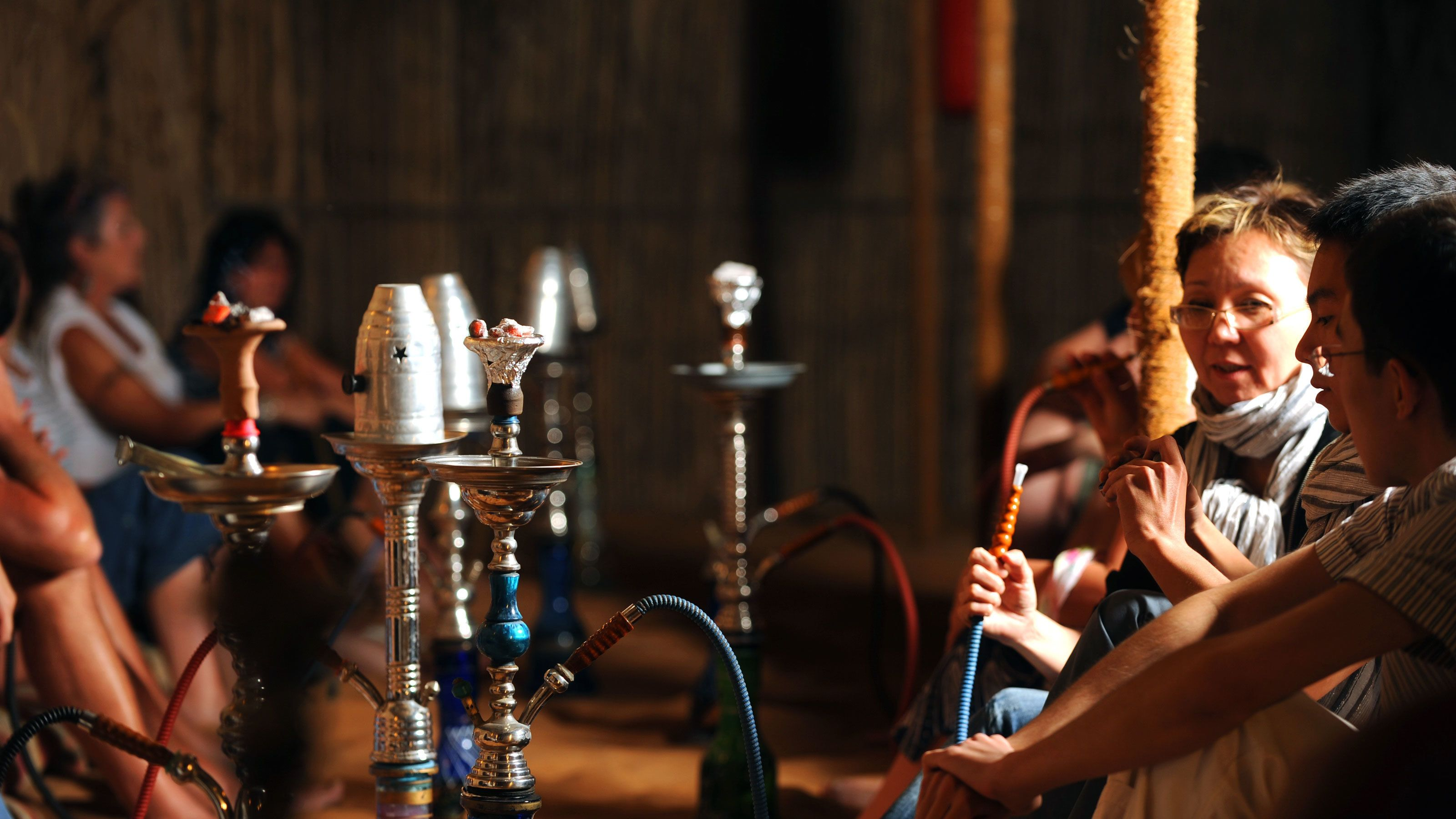 woman and others smoking Arabic sheesha pipe in Dubai