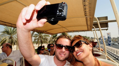 man and woman taking a selfy shot on tour bus in Dubai