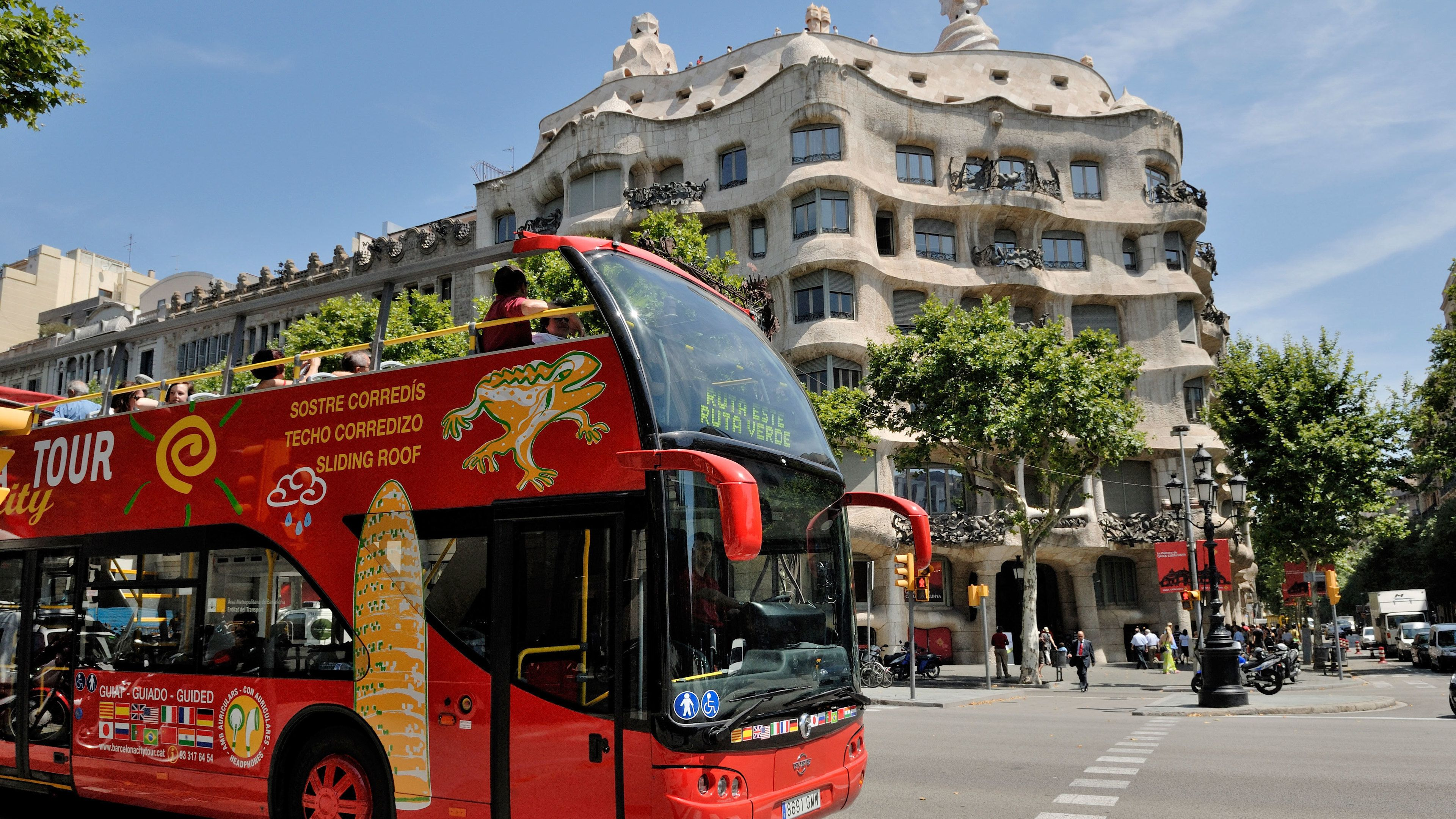 passengers on open air tour bus driving by Casa Batllo? in Barcelona