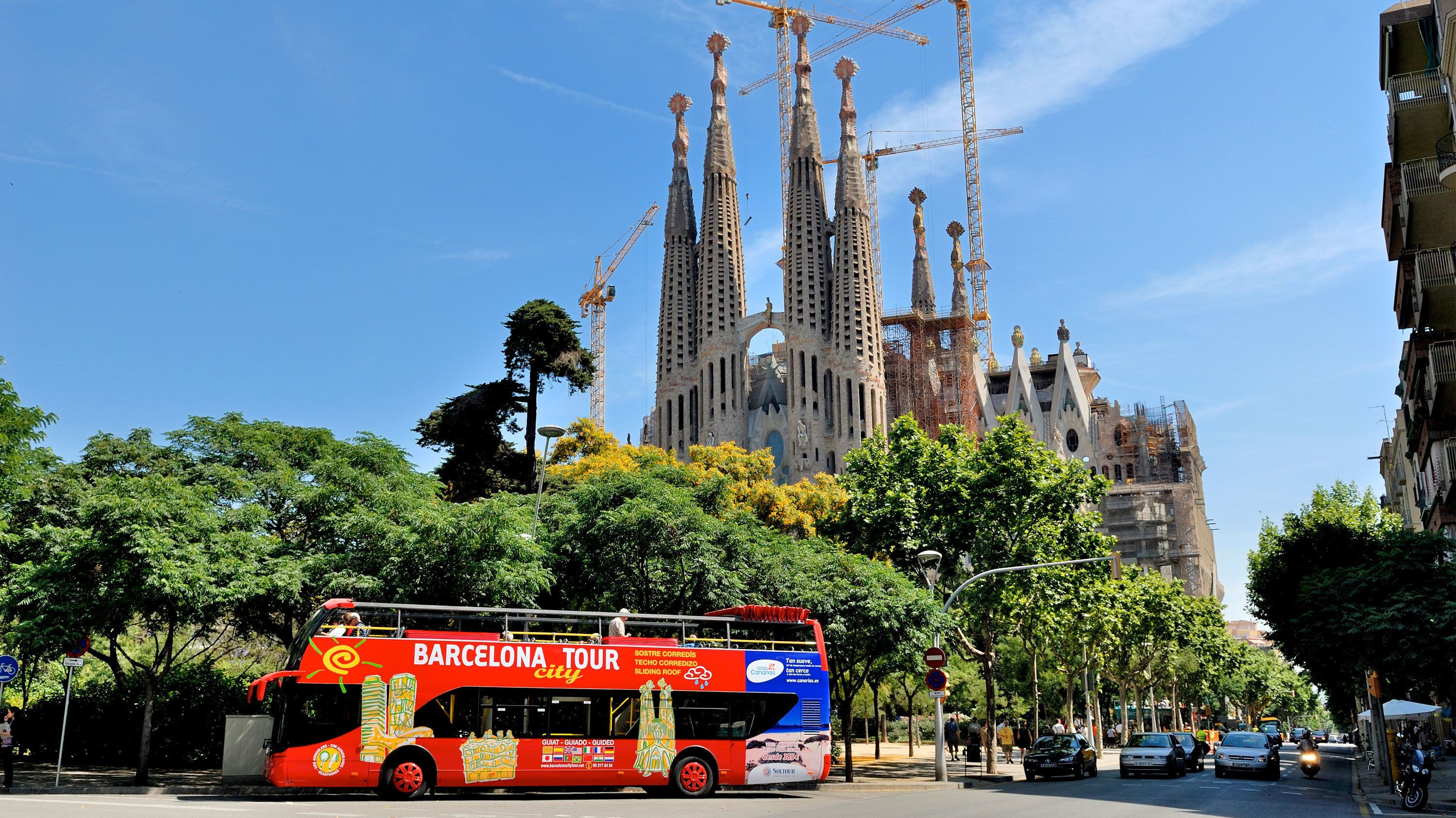 passengers on open air tour bus driving by Sagrada Fami?lia church in Barcelona