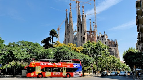 passengers on open air tour bus driving by Sagrada Família church in Barcelona