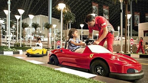 young girl driving Ferrari bumper car at Abu Dhabi Ferrari world