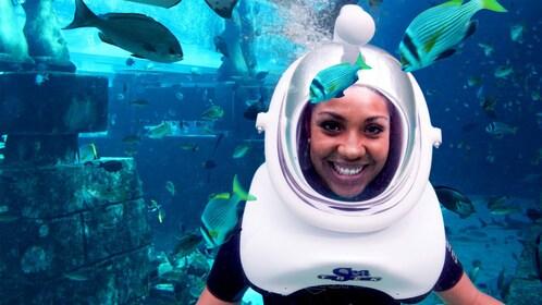 woman in scuba helmet swimming inside aquarium in Dubai