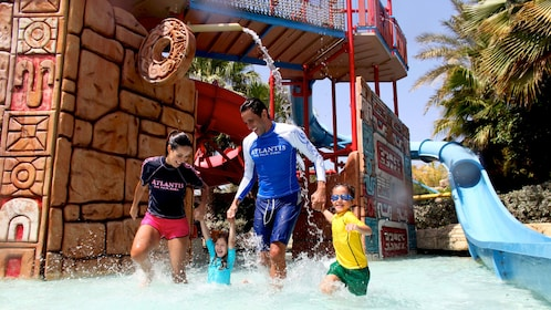 man and woman playing with children in waterpark pool in Dubai
