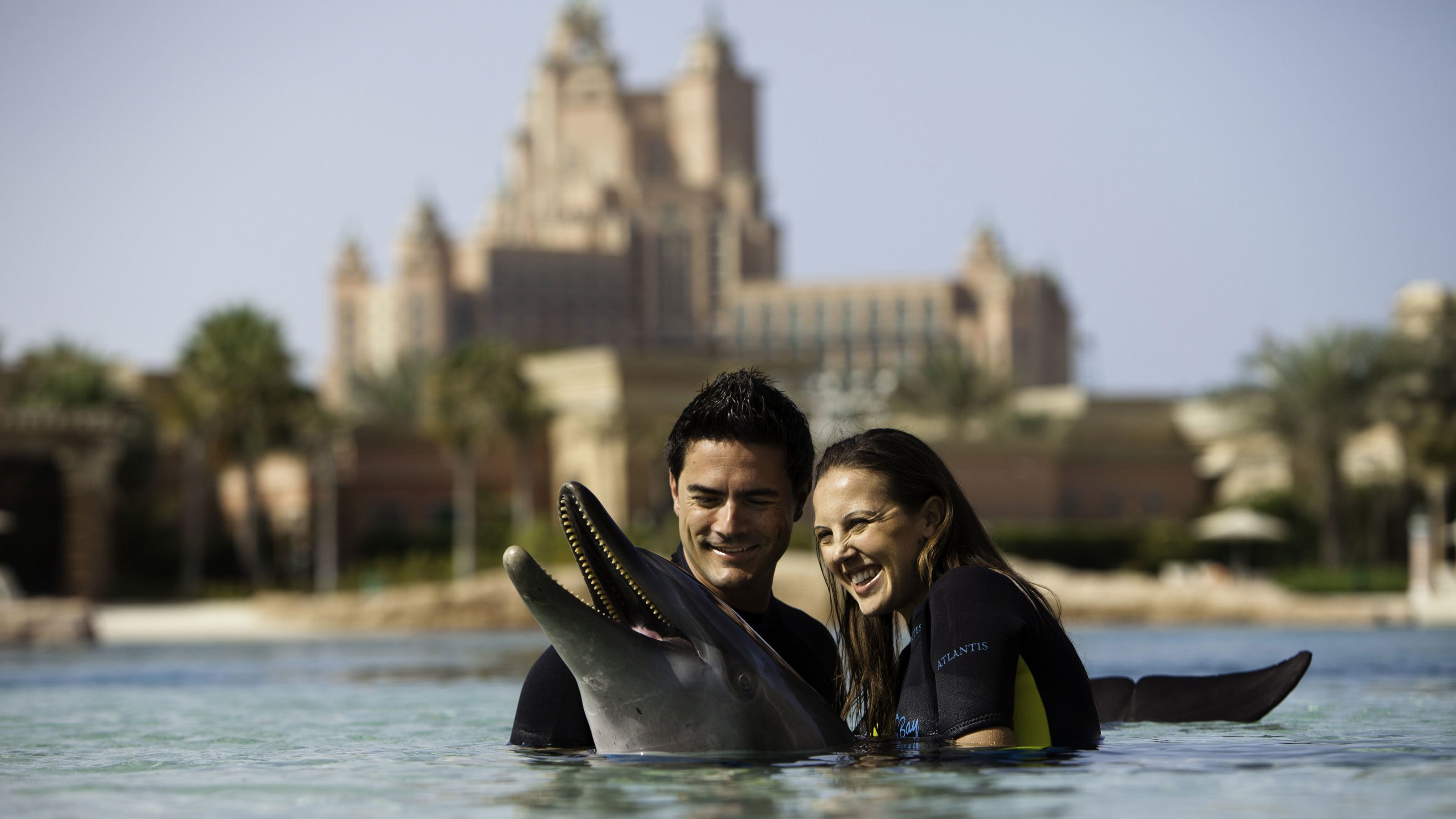 man and woman in water with happy dolphin in Dubai