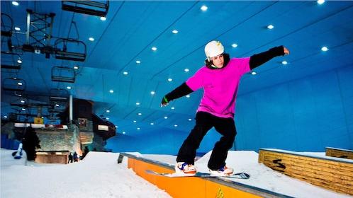 man sliding down rail on snowboard at indoor ski park in Dubai