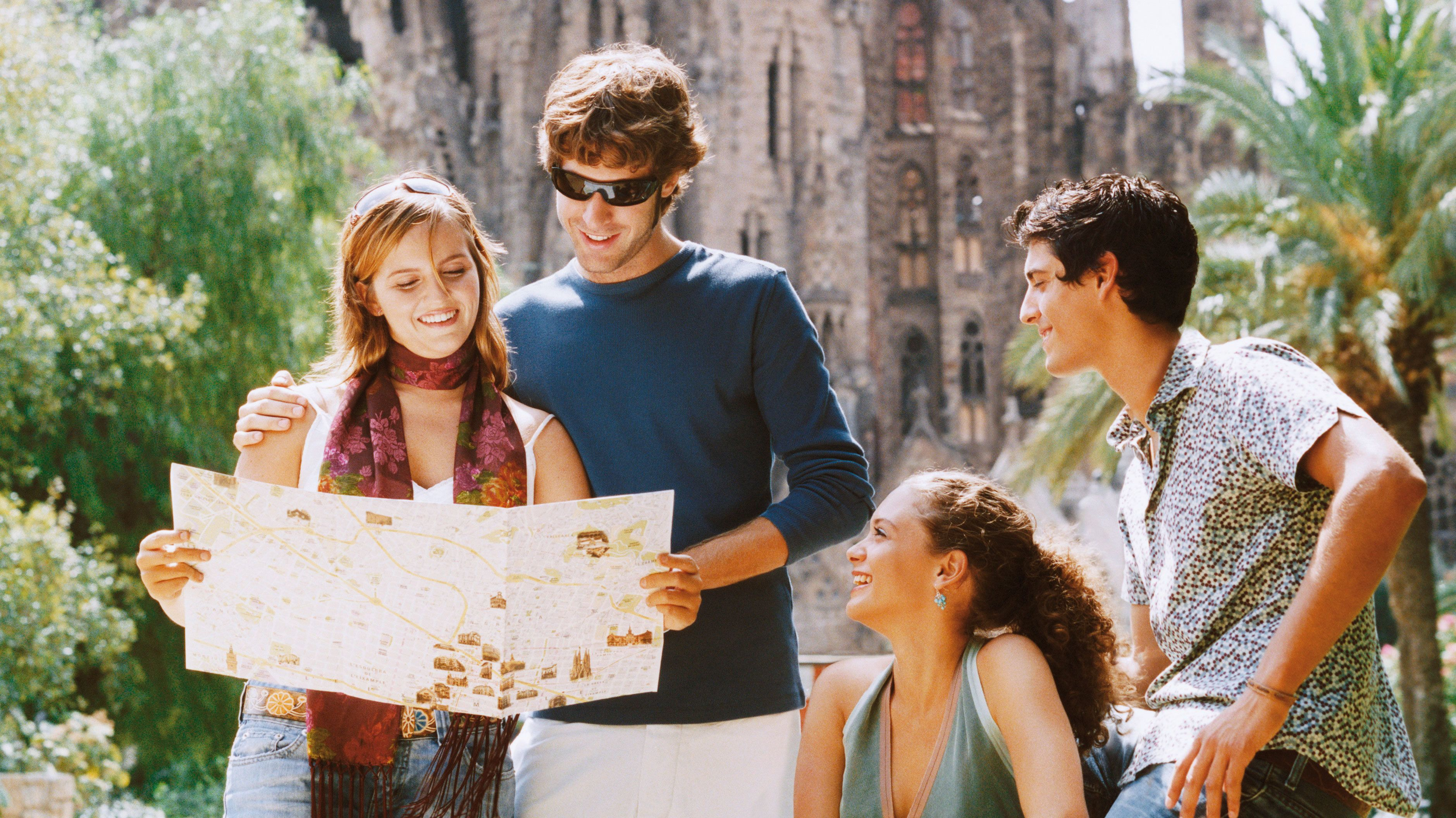 four friends reading tourist map in Barcelona