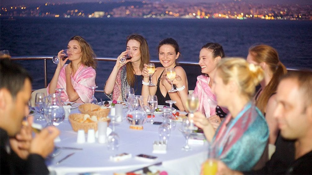 Carregar foto 3 de 5. Guests smiling and enjoying drinks on the Bosphorus Dinner Cruise in Turkey