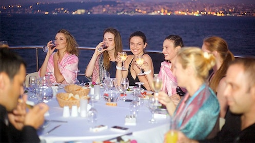 Guests smiling and enjoying drinks on the Bosphorus Dinner Cruise in Turkey