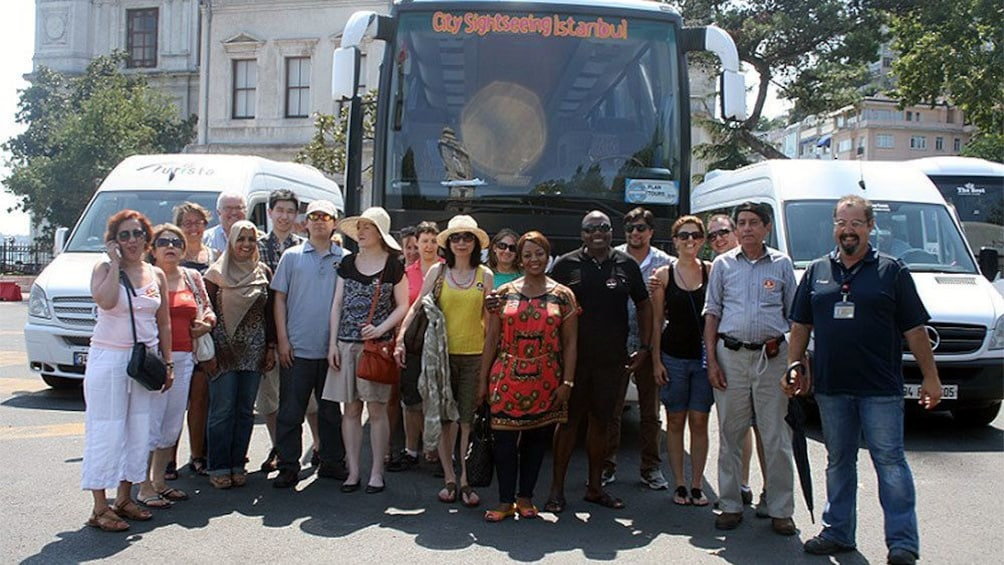 A group of tourists posing for a picture in front of a tour bus in Istanbul