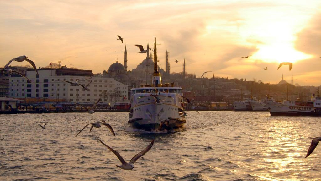 View of the Istanbul ferry going through the water during sunset