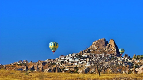 Hot air balloons float in the blue skies above Cappadocia