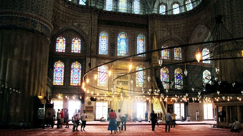 View inside the Blue Mosque in Istanbul with the lights outside shining through the windows