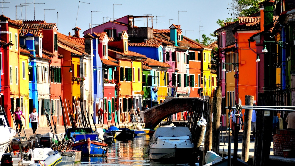 Show item 2 of 10. Canal in with boats and colorful architecture in Venice Italy