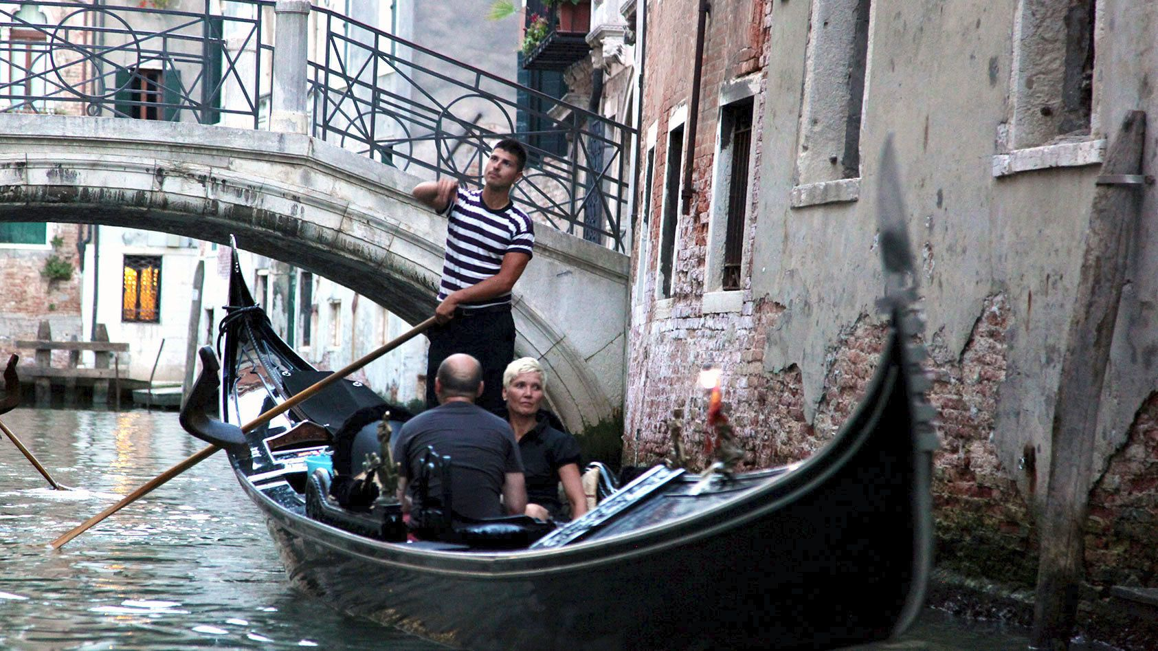 Gondola going under bridge in Venice Italy