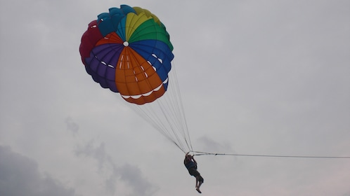 Show item 5 of 5. A person parasailing at Koh Larn Coral Island