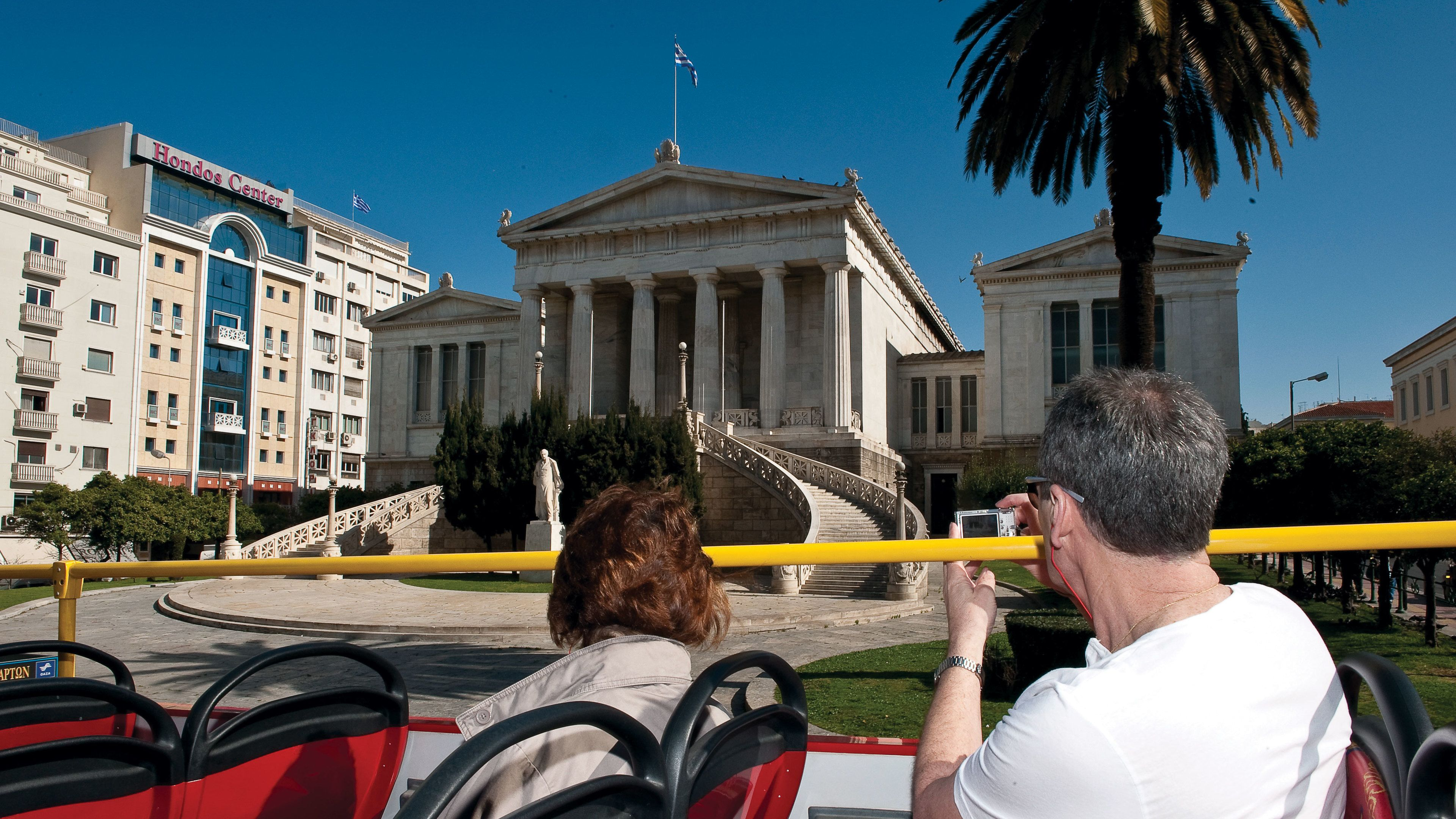 Open-top tour bus with passengers passing the National Library of Greece in Athens