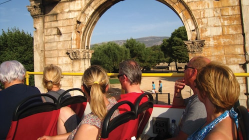 Open-top tour bus at the Arch of Hadrian in Athens