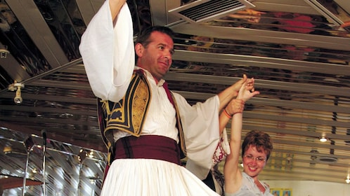 Male dancer leading a woman from the audience in traditional Greek dance
