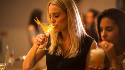 blonde woman sipping cocktails in amsterdam