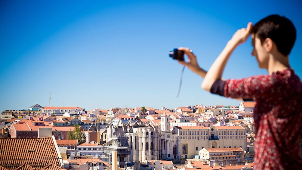 Tourist photographing the Alfama skyline in Lisbon, Portugal