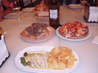 Plated entrees on a table with a bottle of wine in a Madrid restaurant