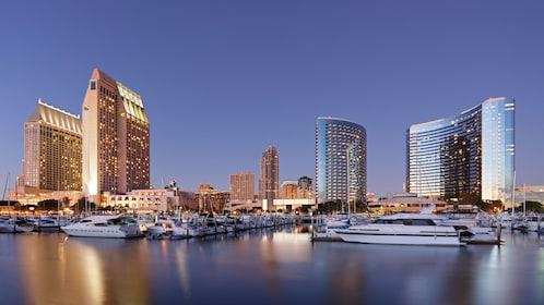 Landscape of bay with ships and skyscrapers at sunset on the San Diego City sightseeing tour in California